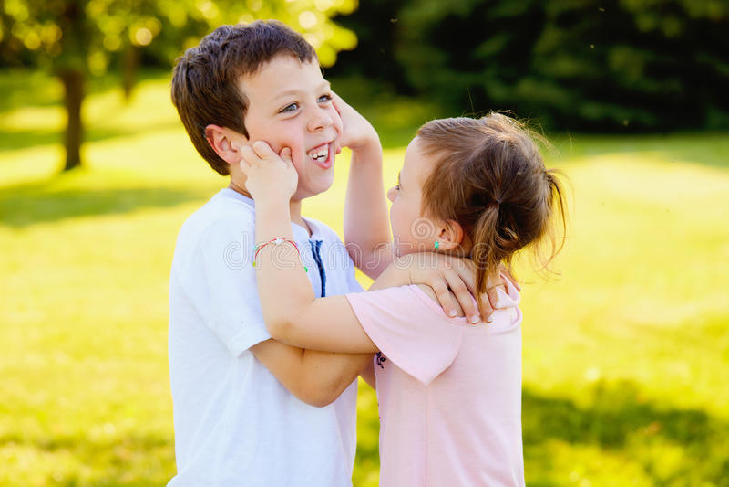 Freches kleines Mädchen, das Backen ihres Bruders klemmt stockfoto