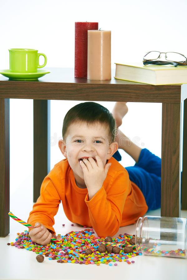 Freches Kleinkind, das Bonbons unter Tabelle isst stockfotos