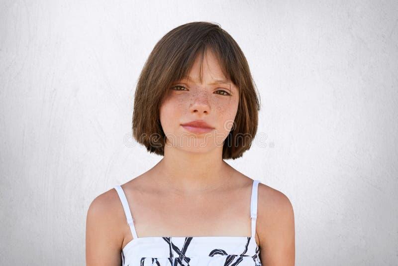 Freckled девушка при карие глаза и темные короткие волосы, смотря с недовольством в камеру пока представляющ против бетонной стен стоковые изображения rf