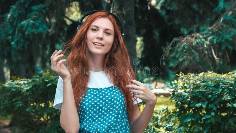 Freckled рыжеволосый подросток слушать музыка в больших наушниках стоковое изображение
