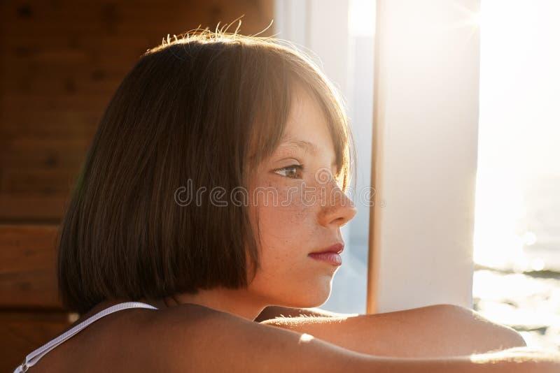 Freckled kind met bobbed kapsel, onderzoekend distanse, het bewonderen mooie overzeese landschappen, dromend over iets Weinig bal stock afbeelding