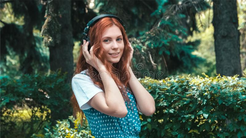 Freckled red-haired teenager listen music in big headphones royalty free stock images