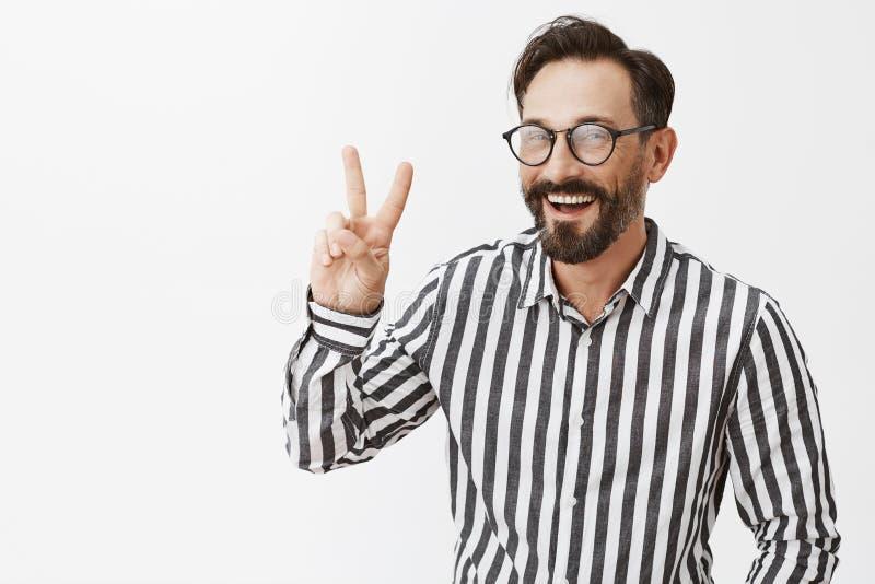 fred Attraktiv vuxen man med skägget och mustasch i exponeringsglas och den formella dräkten som försöker att finna kontakten med royaltyfria foton