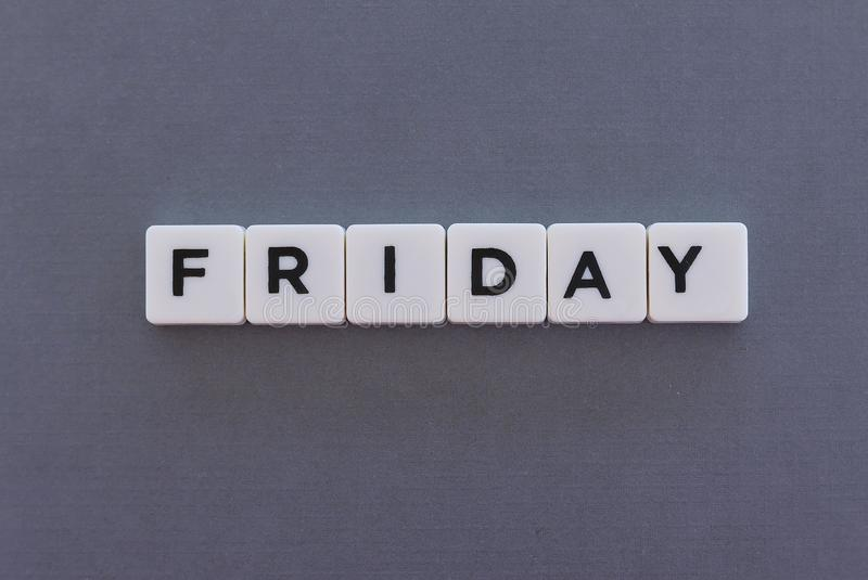 fredag ord som göras av fyrkantigt bokstavsord på grå bakgrund arkivfoto