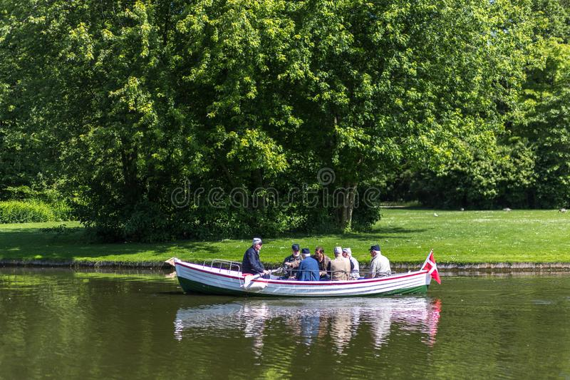 People in a rowboat in Frederiksberg GardensDenmark. Frederiksberg, Denmark - June 17, 2017: Group of people in a rowboat in Frederiksberg Park. Frederiksberg royalty free stock images