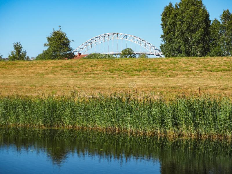 Fredrikstad Bridge in Fredrikstad Norway. The Fredrikstad bridge with fields and waterfront in the foreground in the Norwegian city of Fredrikstad royalty free stock photo