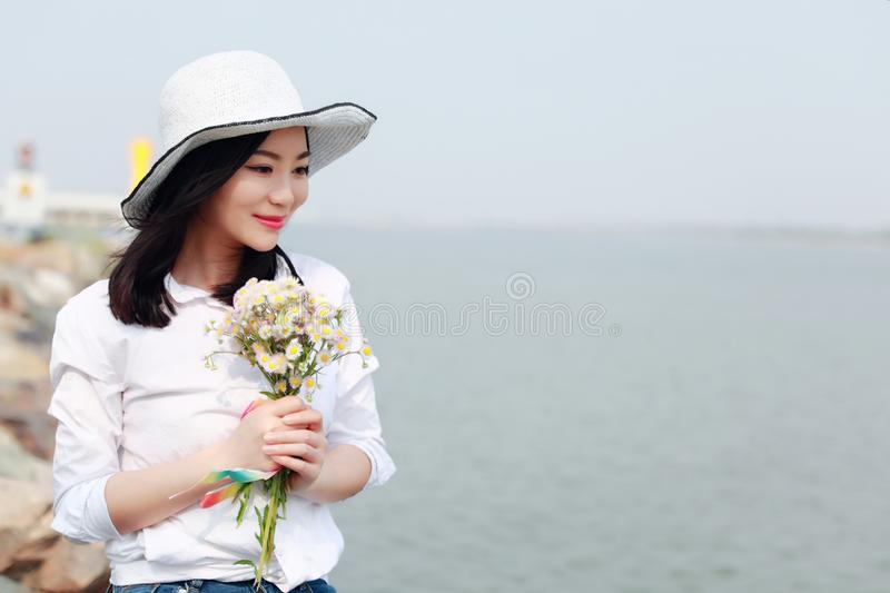 Free careless causual beauty by beach ocean lake river enjoy relax time in summer spring park smile on her face hold a flower stock photo