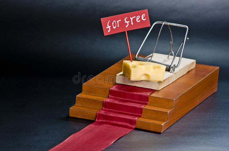 The only free cheese is in the mousetrap: mousetrap with cheese entrapment concept and free sign on the isolated black background. stock image