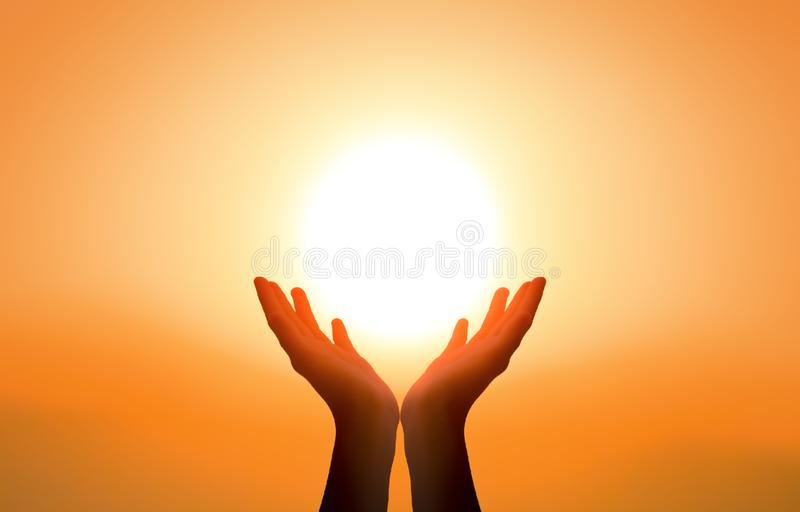Free concept: Raised hands catching sun on sunset sky stock image