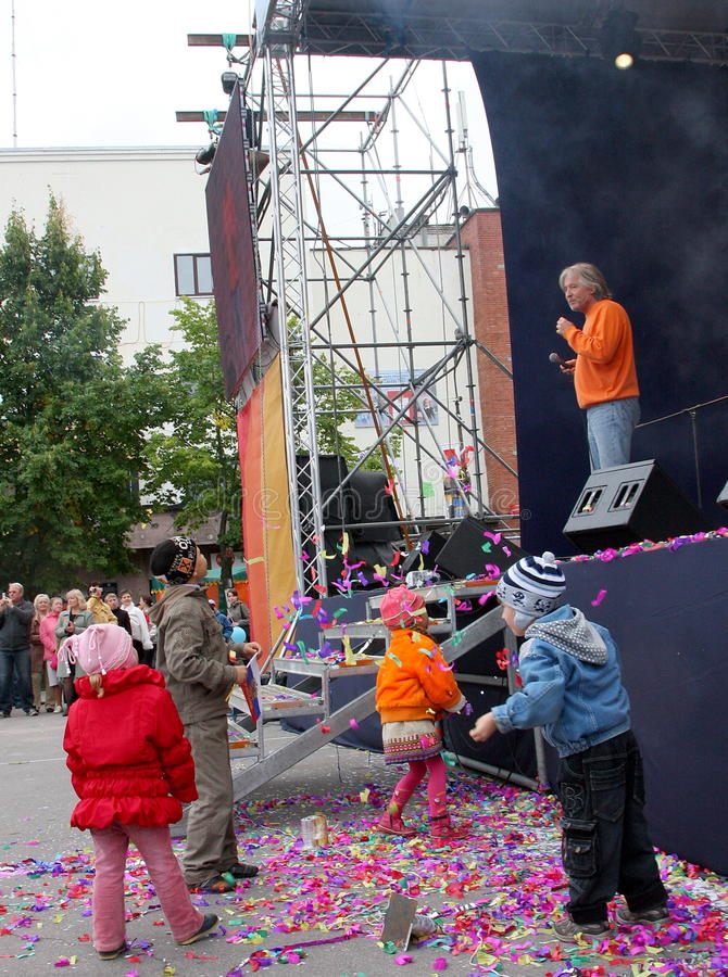 A free concert, singer bard (country rock music), children are playing near the stage and the audience , an open stage stock photo