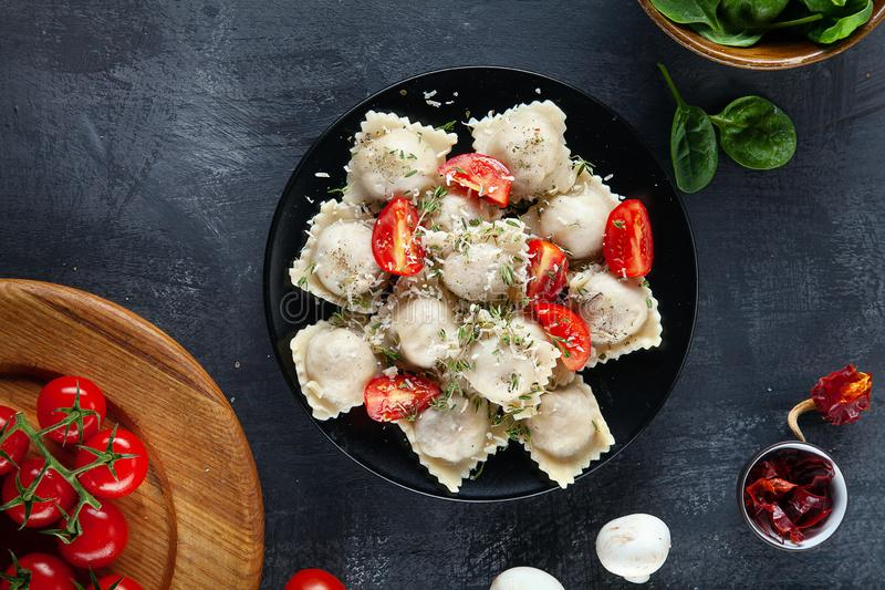 Top view on fresh ravioli with slice cherry tomato on black plate and dark background. royalty free stock photos