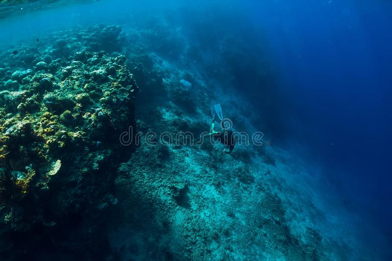 Free diver dive in deep ocean, underwater view with rocks and corals. Freediving royalty free stock photography