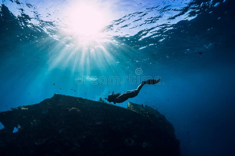 Free diver girl in pink swimwear with fins swimming underwater at wreck ship. Freediving in the ocean royalty free stock photography