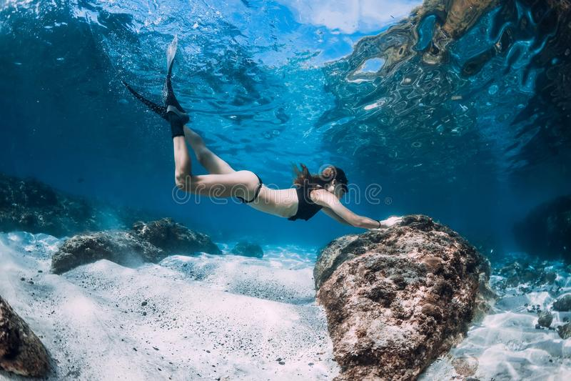 Free diver glides over sandy sea with fins stock image