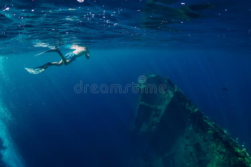 Free diver man swimming in sea near shipwreck in Bali royalty free stock photos