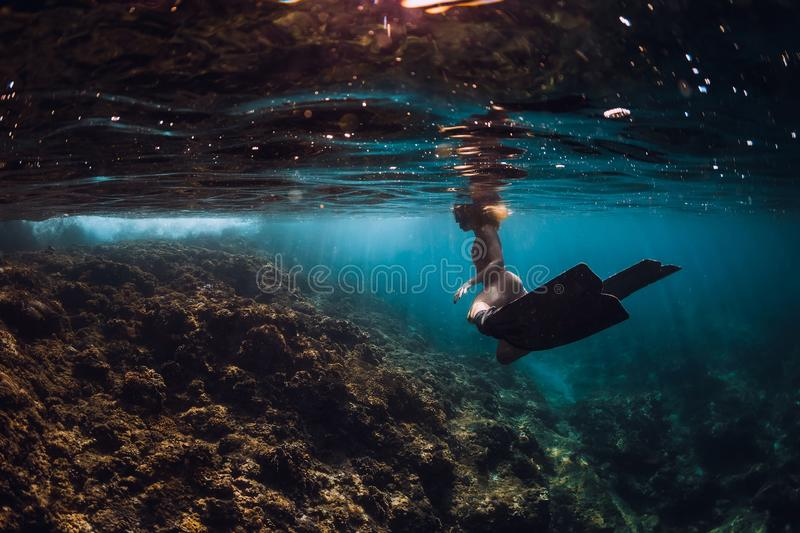 Free diver woman with fins over coral bottom. Freediving underwater in ocean royalty free stock photo