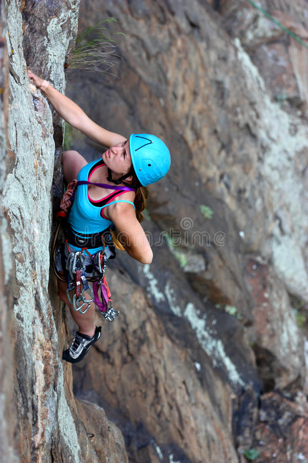 Free female climber. Extreme free female climber claiming a stone wall outdoor stock image