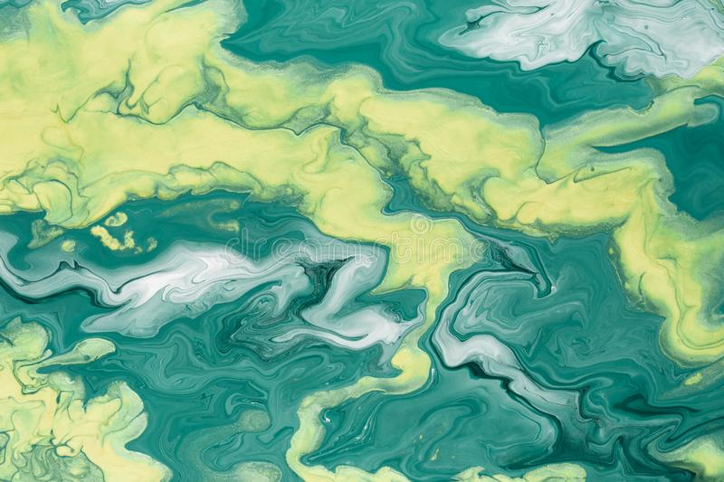 Free flowing yellow and green acrylic paint. Random Waves and Curls. Abstract marble background or texture royalty free stock images