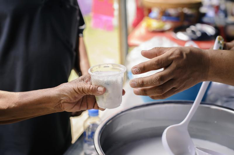 Free food for poor and homeless people donates food to food less people : The poor have been sharing food from the kinder society. To Relieve Hunger : Social stock images