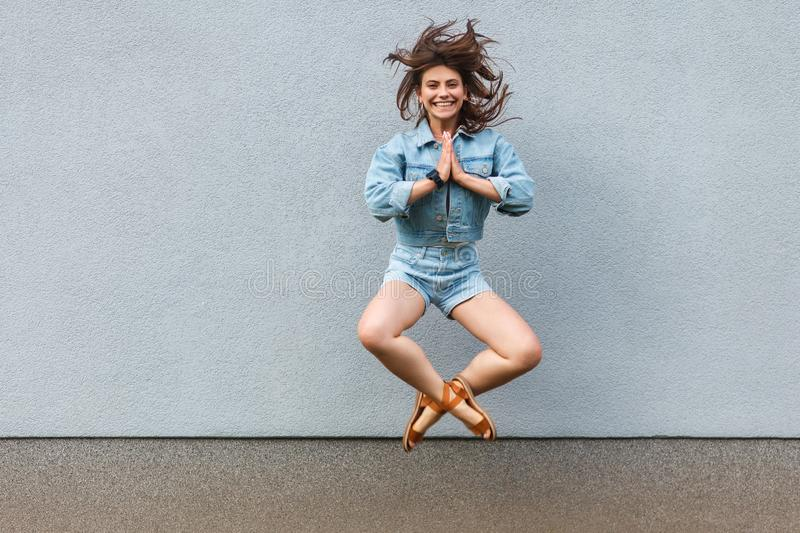 Free happy beautiful woman in casual jeans denim style in summertime jumping at light blue wall with namaste palm hands and royalty free stock image