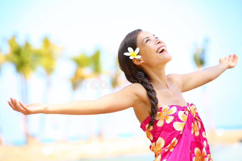 Free happy elated beach woman in freedom joy concept. Beautiful girl smiling with arms out looking up joyful on Hawaiian beach. Mixed race Asian / Caucasian stock images