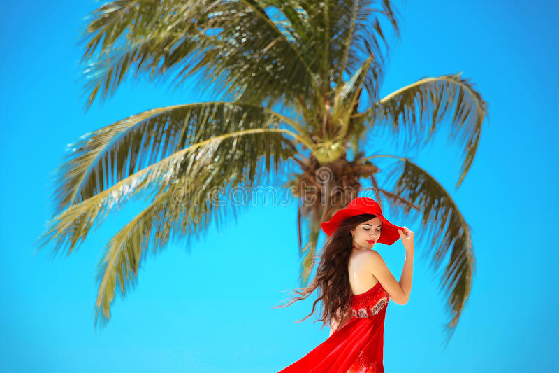 Free Happy Woman Enjoying Nature. Beauty Girl with red hat, summer Outdoor. Freedom concept. Beauty Girl over Sky and Sun. royalty free stock photo