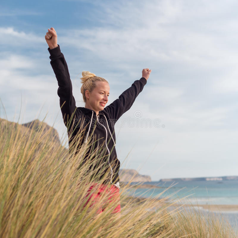 Free Happy Woman Enjoying Sun on Vacations. Active sporty woman, arms raised, enjoying sun, freedom and life an a beautiful beach. Young lady feeling free stock photography