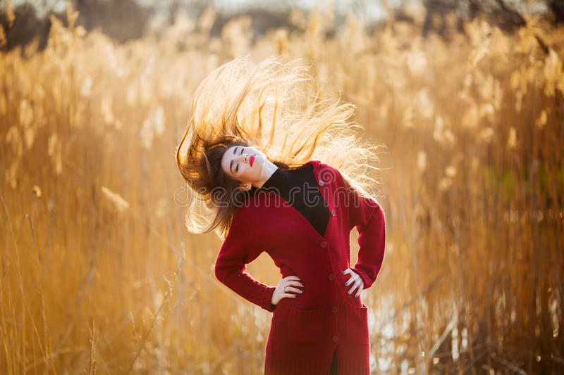 Free happy young woman. Beautiful female with long healthy blowing hair enjoying sun light in park at sunset. Spring stock photos