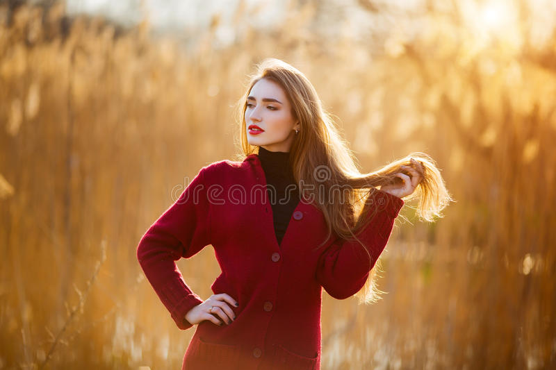 Free happy young woman. Beautiful female with long healthy blowing hair enjoying sun light in park at sunset. Spring royalty free stock photography
