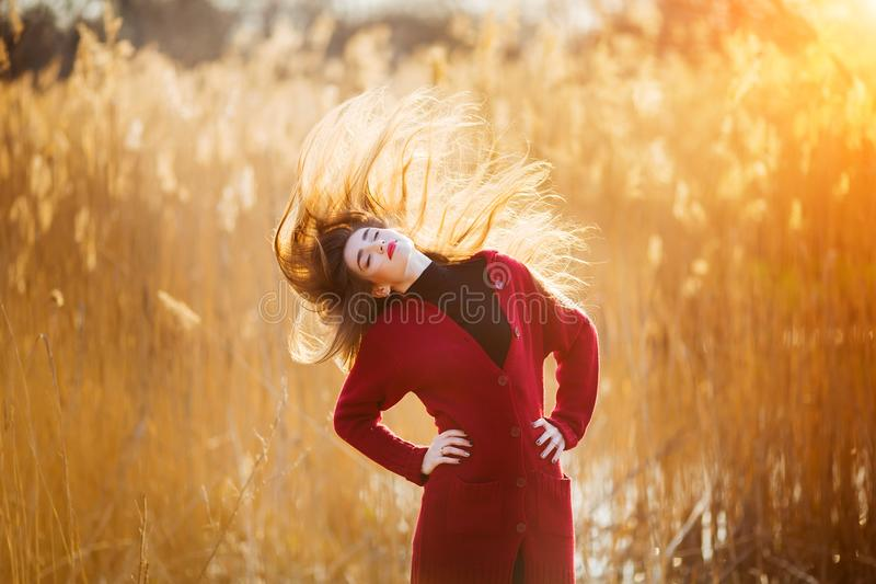 Free happy young woman. Beautiful female with long healthy blowing hair enjoying sun light in park at sunset. Spring royalty free stock image