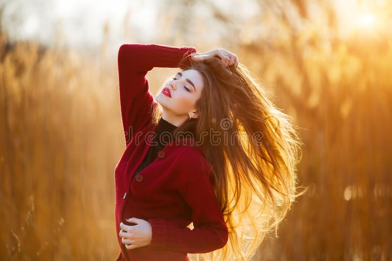 Free happy young woman. Beautiful female with long healthy blowing hair enjoying sun light in park at sunset. Spring stock photo