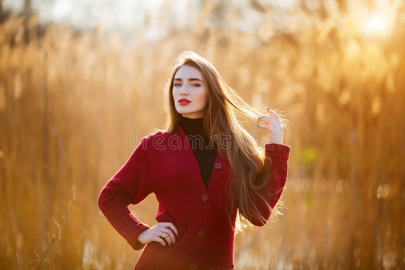 Free happy young woman. Beautiful female with long healthy blowing hair enjoying sun light in park at sunset. Spring royalty free stock photos