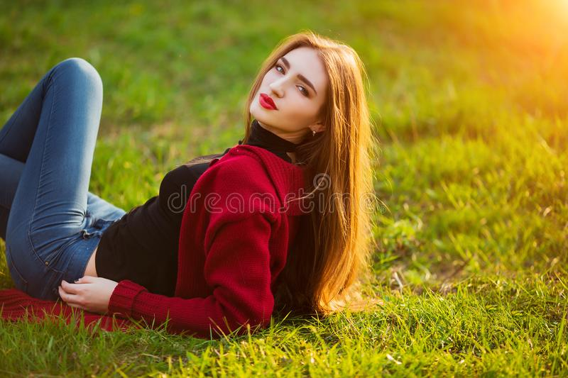 Free happy young woman. Beautiful female with long healthy hair enjoying sun light in park at sunset. Spring, autumn stock image