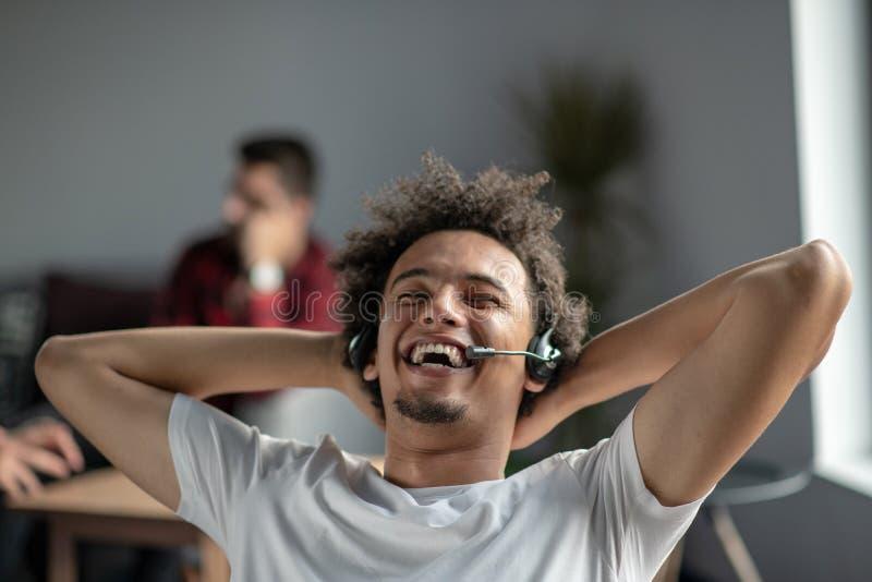Free lance afroamericane rilassate soddisfatte che ritengono felici sul lavoro che si siede alla scrivania con la cuffia avricola immagini stock libere da diritti