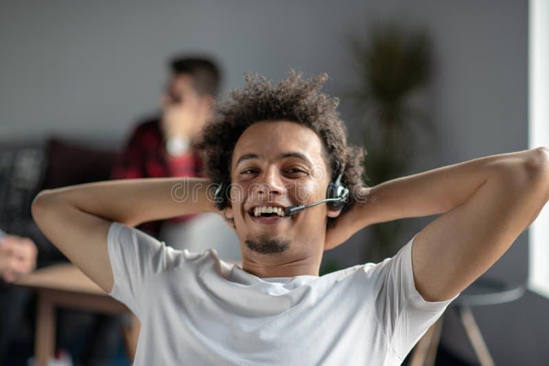 Free lance afroamericane rilassate soddisfatte che ritengono felici sul lavoro che si siede alla scrivania con la cuffia avricola fotografie stock libere da diritti