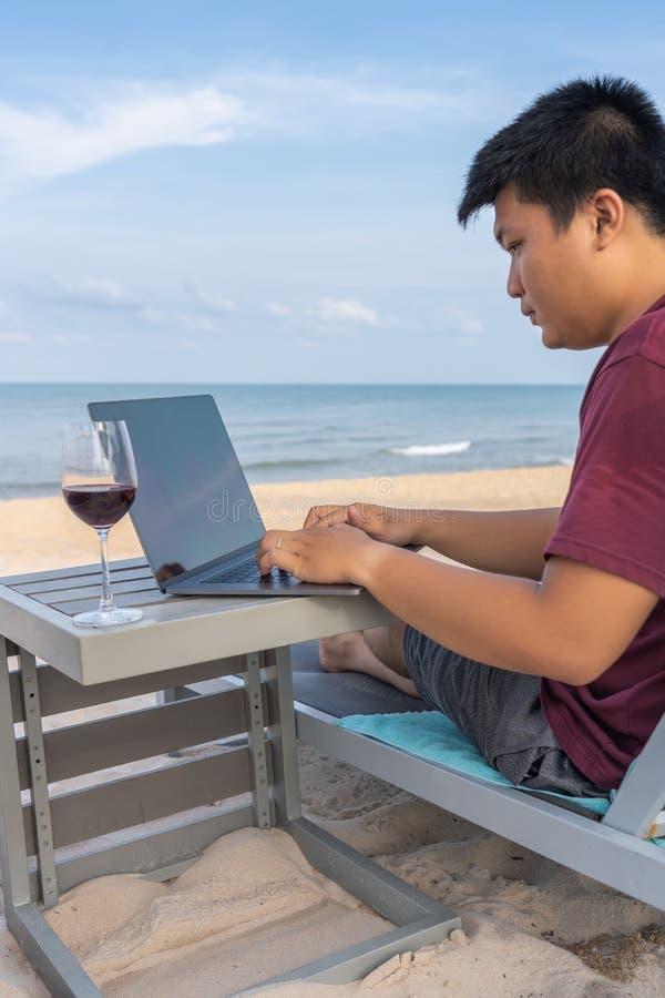 Free lance asiatiche che lavorano con il computer portatile sulla spiaggia di sabbia bianca tropicale fotografie stock