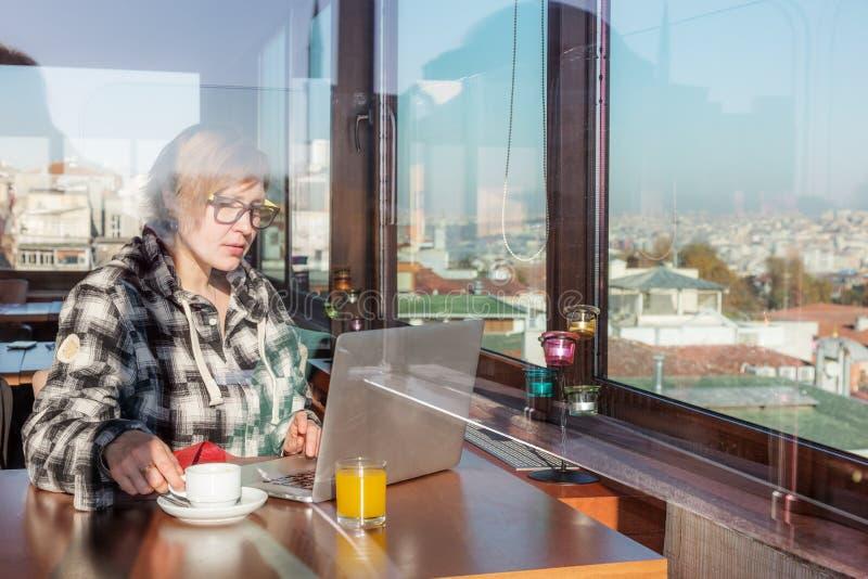 Free lance che lavorano al computer portatile che si siede al caffè con la vista della città immagini stock libere da diritti
