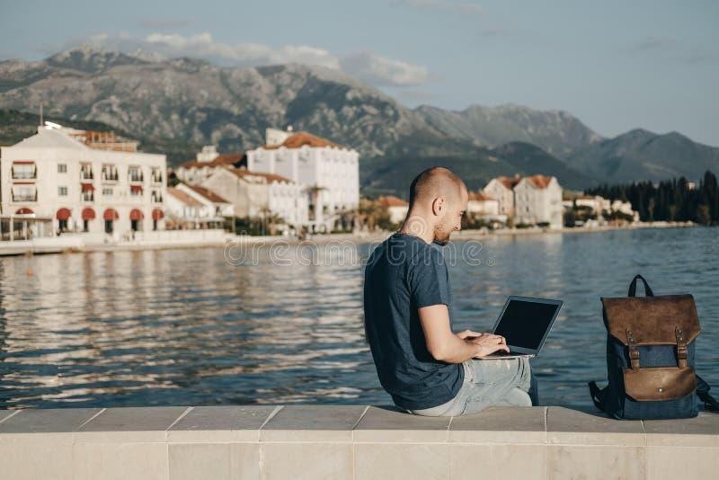 Free lance del giovane che lavorano con il computer portatile che si siede vicino al mare, copia immagine stock libera da diritti