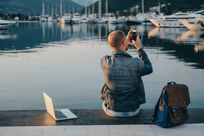 Free lance del giovane che lavorano con il computer portatile e che prendono sitti della foto immagine stock libera da diritti