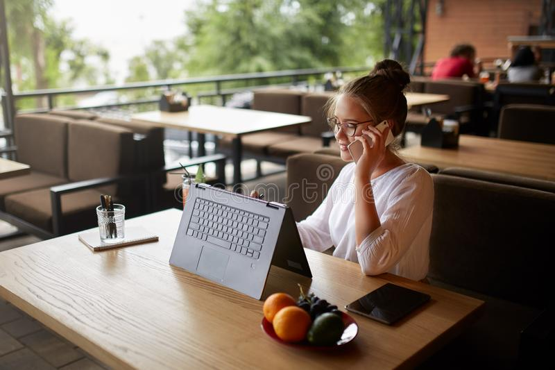 Free lance della corsa mista che lavorano con il computer portatile convertibile e che parlano sul cellulare con il cliente in ca immagine stock libera da diritti