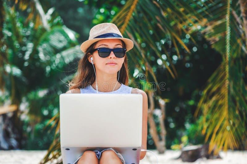 Free lance della giovane donna che lavorano in computer portatile sulla spiaggia Freelance il lavoro fotografia stock libera da diritti