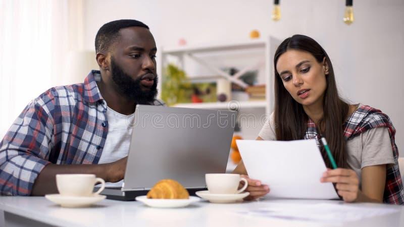 Free lance multirazziali che lavorano al progetto a casa facendo uso del computer portatile, gestione fotografie stock libere da diritti
