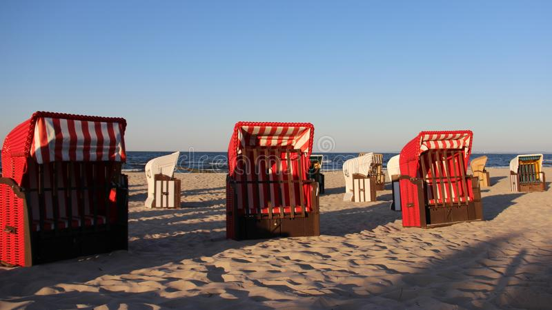Red Colorful Local Beach Chair On Baltic Seaside With Evening light. Free and Quiet. Colored Local Traditional beach chair with warm sunshine and blue sky royalty free stock photography