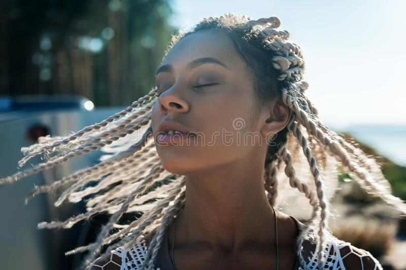 Close up woman with dreadlocks feeling free and relaxed in nature. Free and relaxed. Close up beautiful cheerful woman with dreadlocks feeling free and relaxed royalty free stock photo