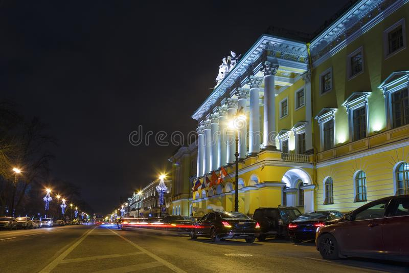 Free road near hotel historical building, Neva embankment, Saint Petersburg. Free road near illuminated hotel historical building. Neva embankment at night stock photo