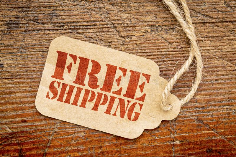 Free shipping sign on a price tag. Free shipping sign - a paper price tag against rustic red painted barn wood royalty free stock photography