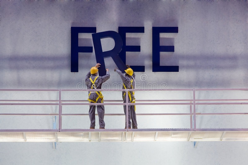 Free sign. Workers preparing a billboard with the word free while standing on a scaffold royalty free stock photography