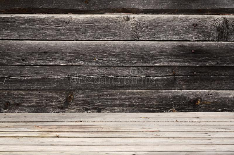 Free space above the wooden surface from horizontal boards against the background of a dark wooden wall. Place for product presen stock photos