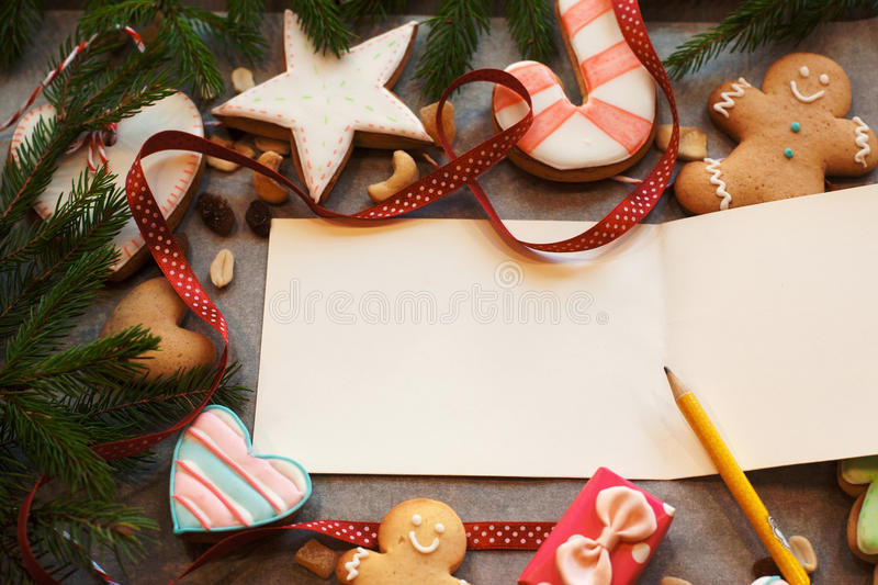 Free space on New year greeting card. Empty postcard in traditional Christmas frame of gingerbread cookies and pine tree branch royalty free stock photos