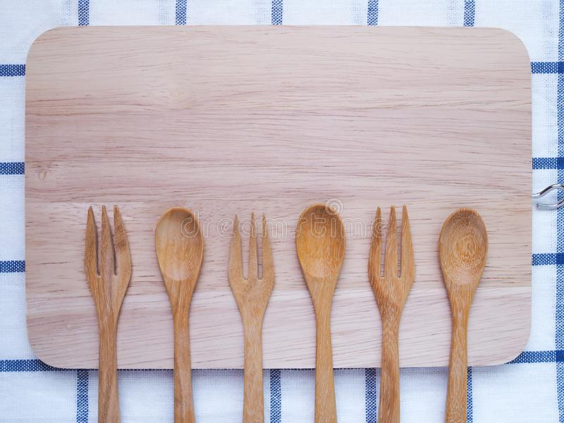 Top view of wooden cutlery, spoon and fork on cutting board. stock photography